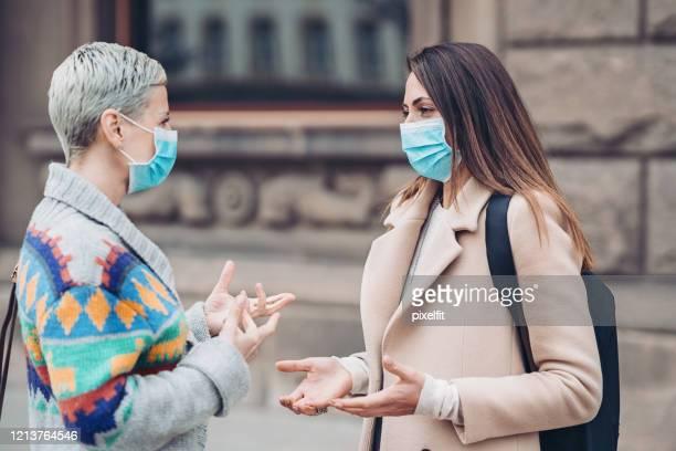freundinnen sprechen draußen während der virusepidemie - atemschutzmaske stock-fotos und bilder