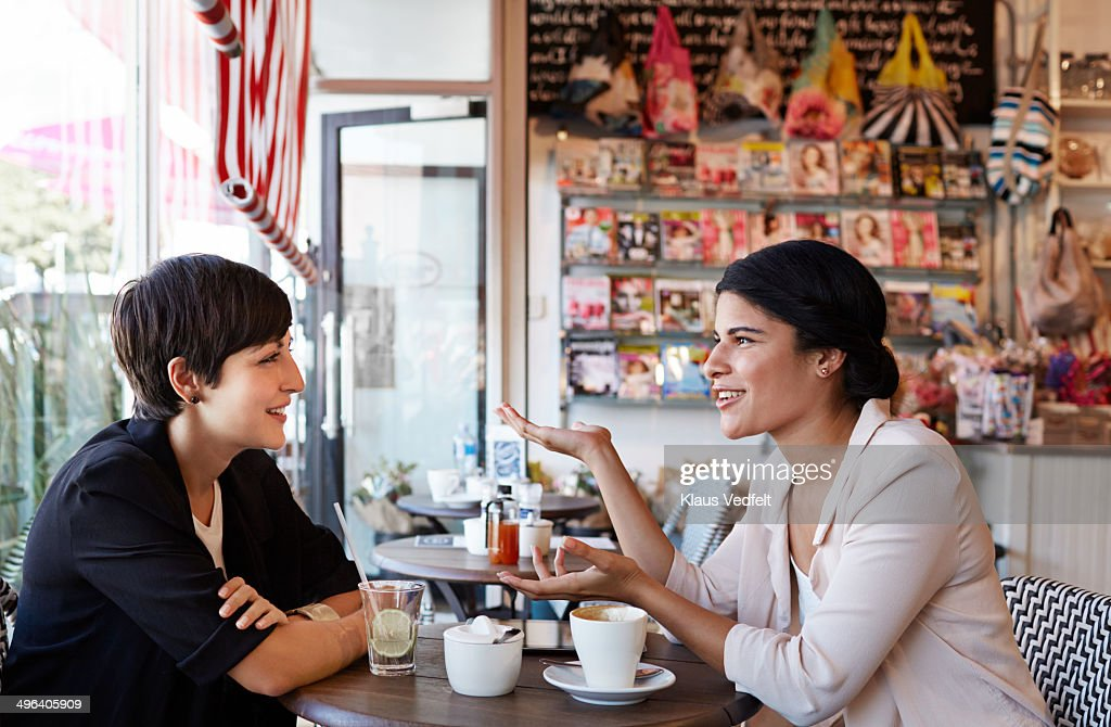 Girlfriends talking over a coffee at café : Stock Photo