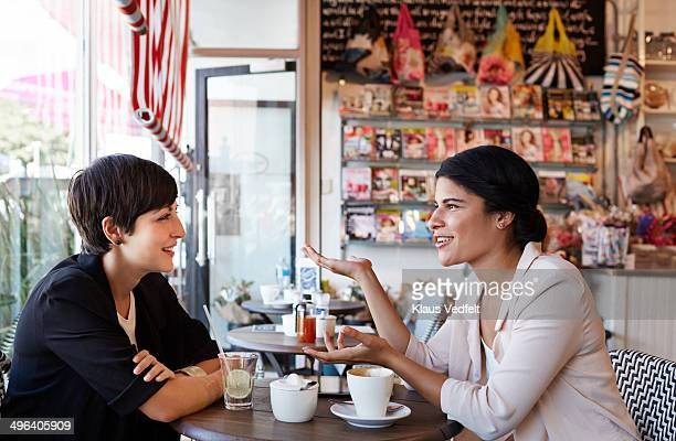 Girlfriends talking over a coffee at café