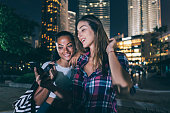 two beautiful girls texting laughing outdoor