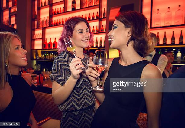 Girlfriends toasting with drinks in nightclub