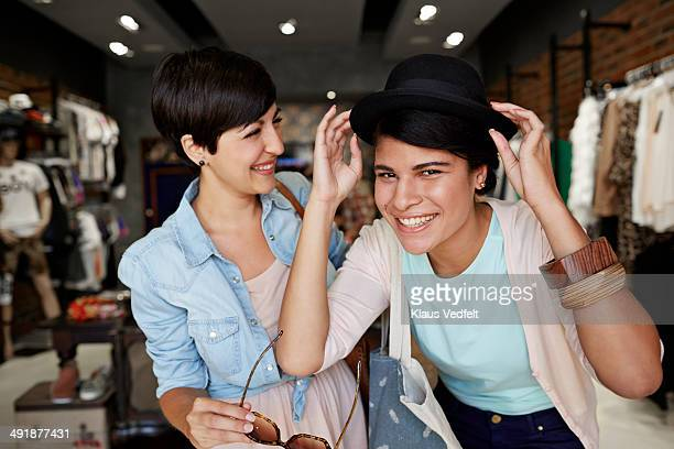 Girlfriends trying hat & sunglasses in shop