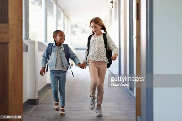 girlfriends walking hand in hand on school isle - only girls stock pictures, royalty-free photos & images