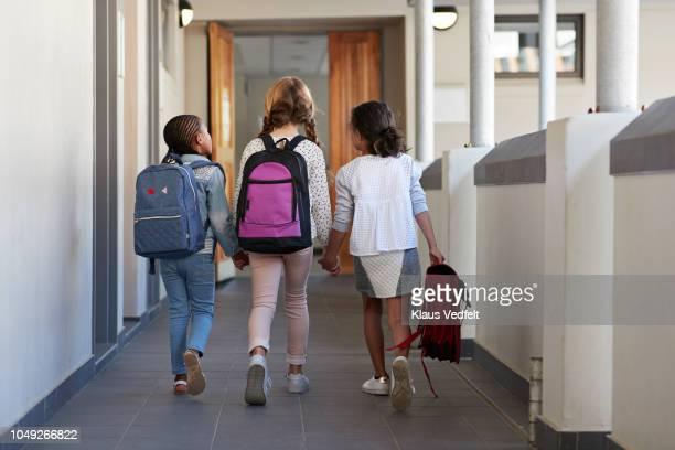 girlfriends walking hand in hand on school isle - basisschool stockfoto's en -beelden