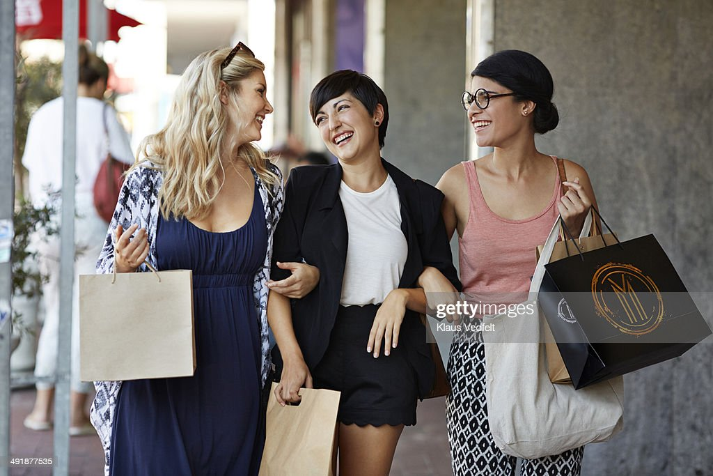 Girlfriends walking together with shopping bags : Stock Photo