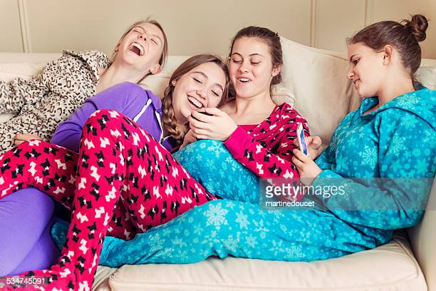 Girlfriends wearing onesies laughing on a couch with mobile phones.