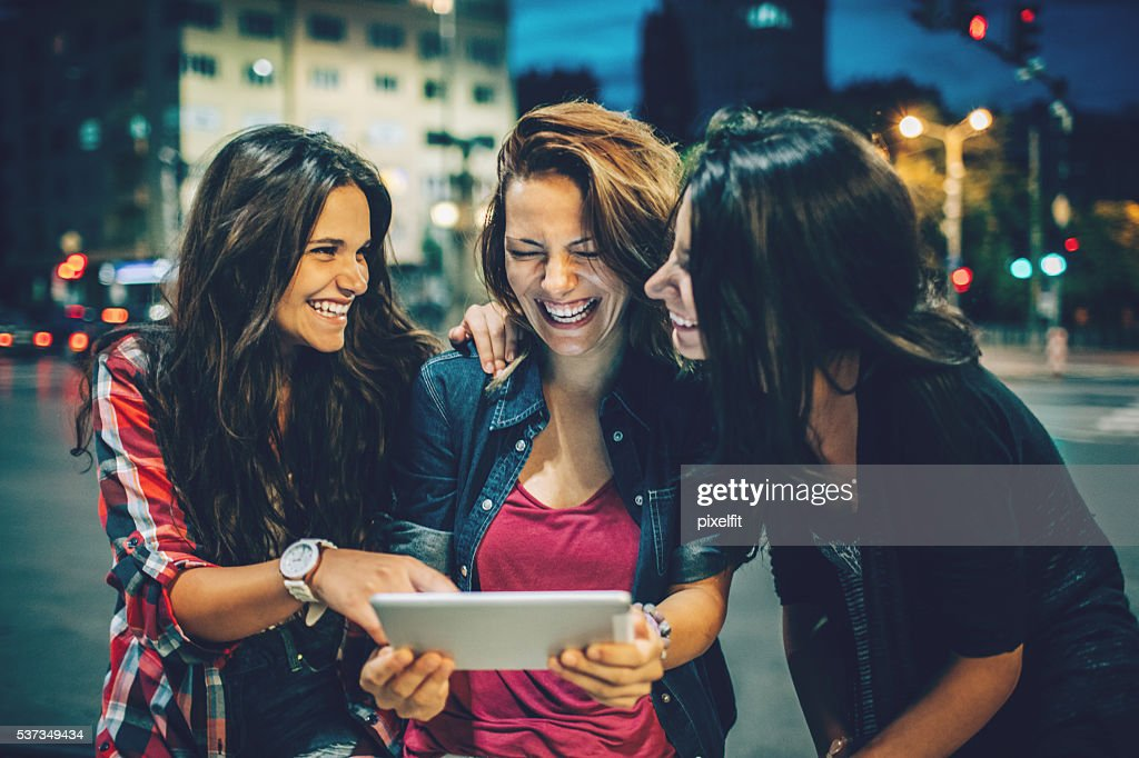 Girlfriends with digital tablet out at night : Stock Photo