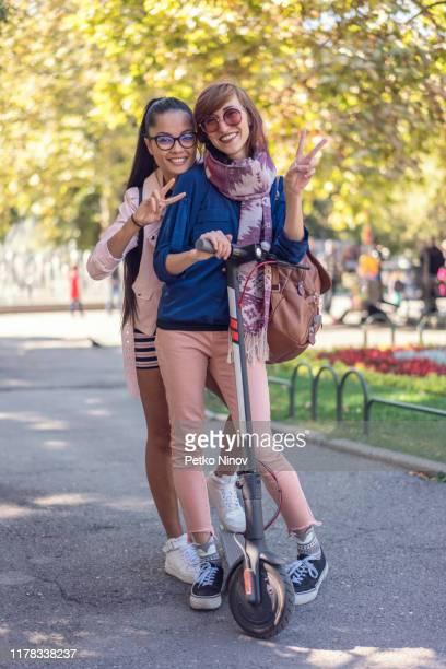 カメラを見て電子スクーターを持つガールフレンド - %e... ストックフォトと画像