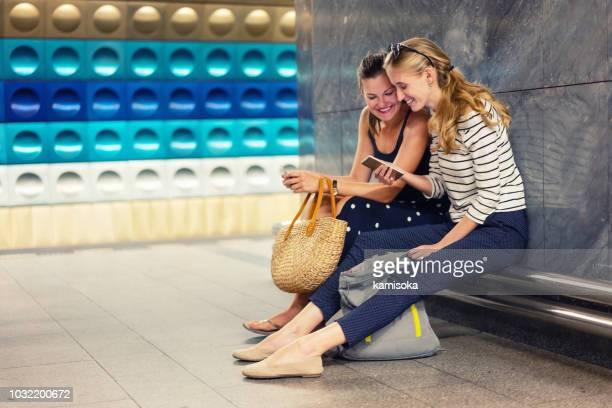 freundinnen mit handy in der u-bahn-station warten - öffentliches verkehrsmittel stock-fotos und bilder