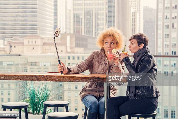 Girlfriends with selfie stick on a roof in New York.
