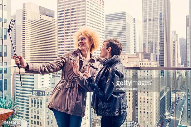 "girlfriends with selfie stick on a roof in new york. - ""martine doucet"" or martinedoucet stock pictures, royalty-free photos & images"