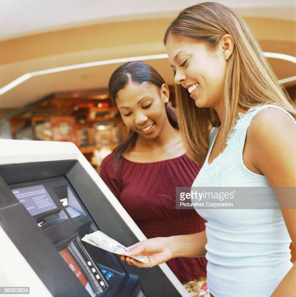 Girlfriends withdraw money from an ATM