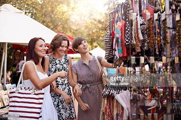 3 Girlfriens looking at clothes at market