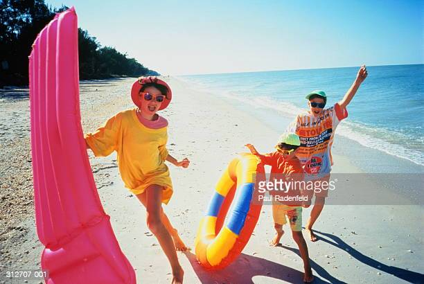 girl(8-10)holding air-bed,with brothers(4-7),on tropical beach - generic location stock pictures, royalty-free photos & images