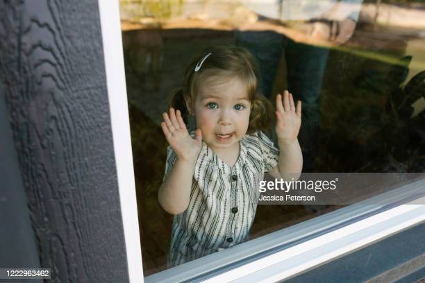 girl (2-3) looking through window - arms raised stock pictures, royalty-free photos & images