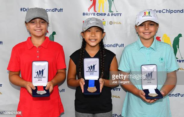 Girls 10-11 age group overall contest top three, second place Mia Hammond, first place Beka Yang, and third place Kate Sowers, pose with their medals...