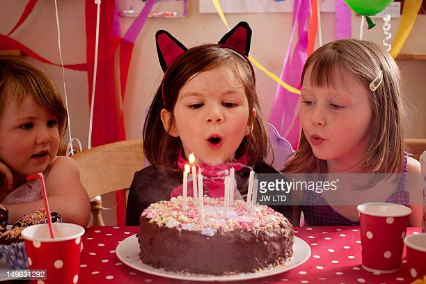 girls 6-7 years, 4-5 years blowing out candles on - 6 7 years stock pictures, royalty-free photos & images