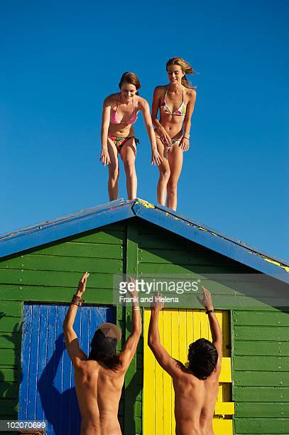 Girls about to climb off beach hut roof