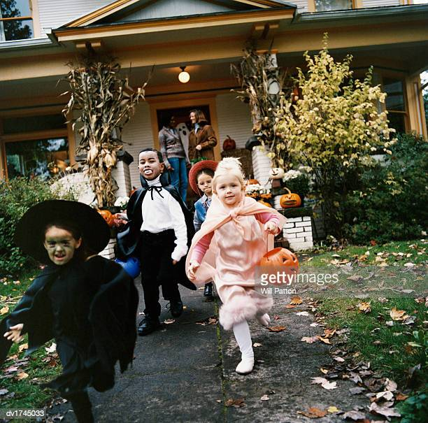 Girls and a Boy in Halloween Costumes Run From Their House