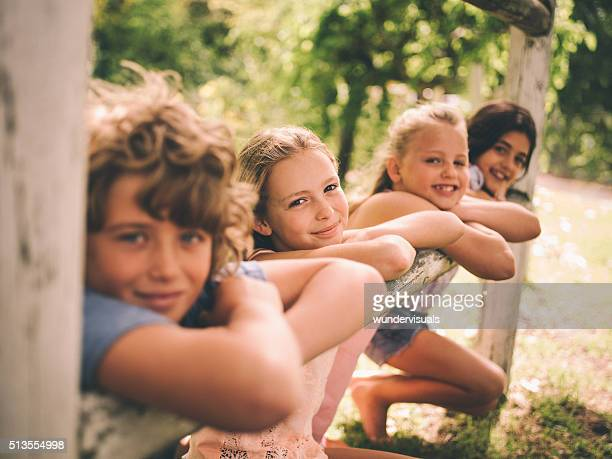 Girls and boy leaning on wooden fence on summer day