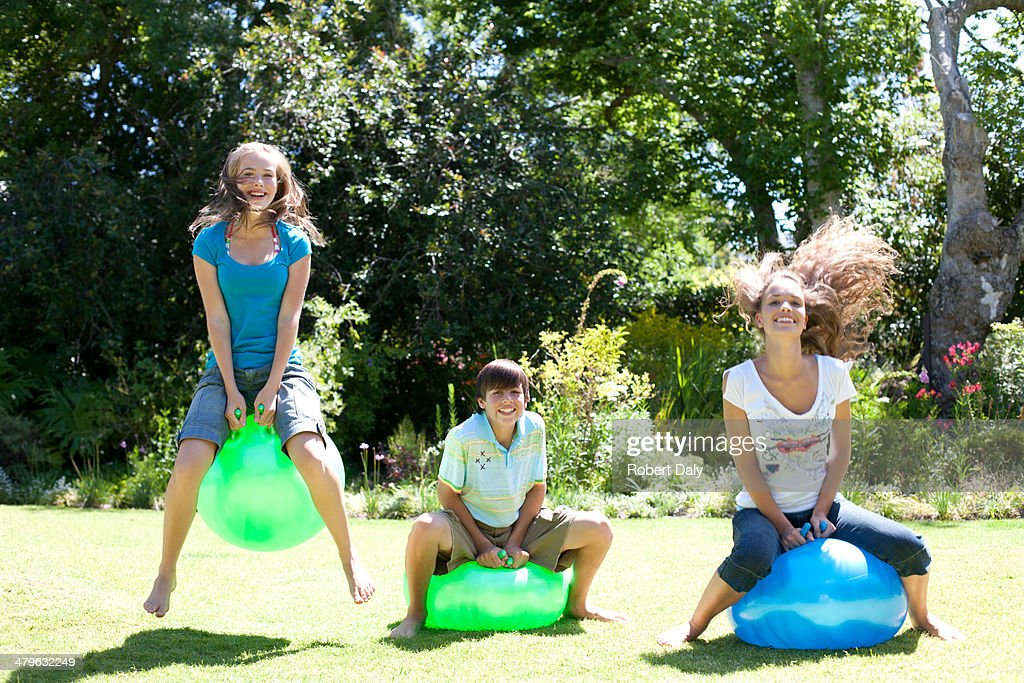 Girls and boy playing on beach balls outdoors : Stock Photo