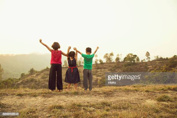 Girls and boy with arms raised on rural field