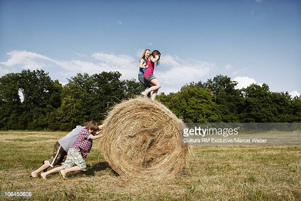 Girls and boys playing with bale of hay