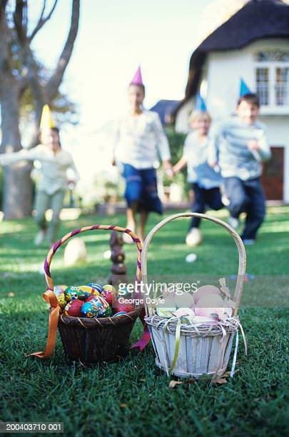 Girls and boys (7-10) running towards basket of Easter eggs on lawn