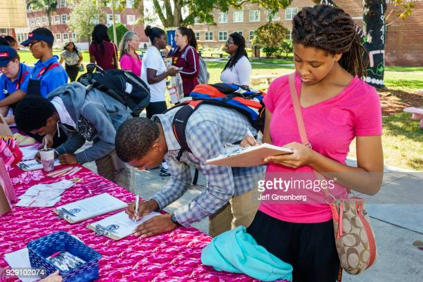 Girls and boys signing up for Breast Cancer Awareness Week at Bethune-Cookman University.