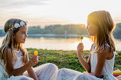 two cute sisters sitting sunset eating