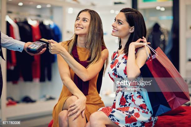 Girls are paying using crdit card in a boutique