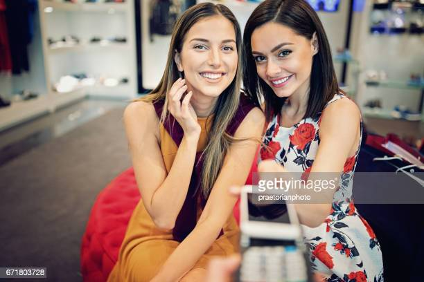 Girls are paying using mobile phone in a boutique