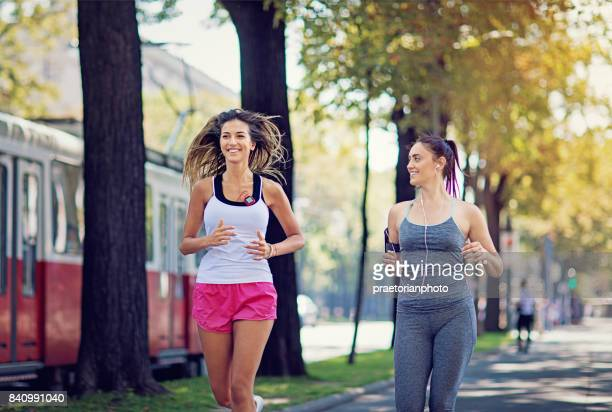 girls are running on a city boulevard - boulevard stock pictures, royalty-free photos & images