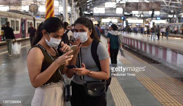 Girls are seen wearing protective mask as a precaution from Coronavirus at CST railway station, on March 14, 2020 in Mumbai, India. The Delhi...