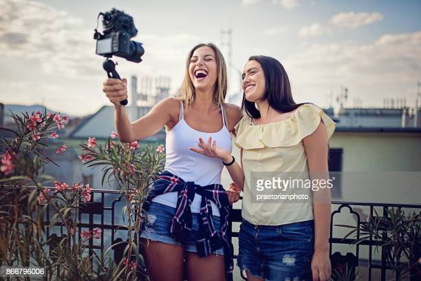 girls are vlogging on the roof terrace - very young webcam girls stock photos and pictures