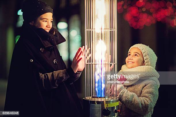 Girls are warming their hands on the gas heater