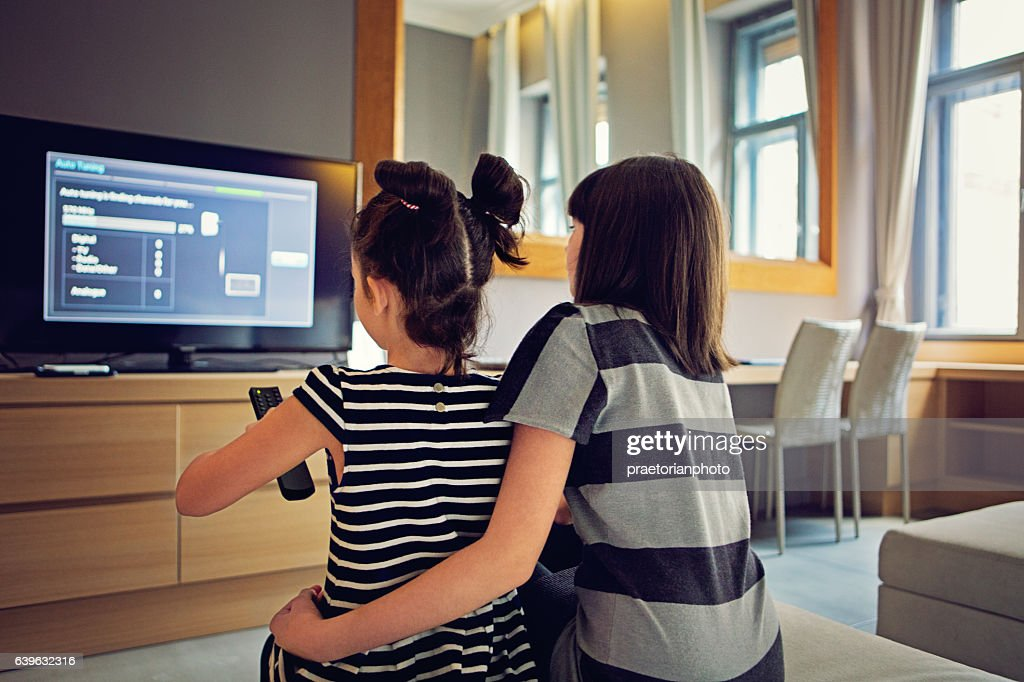 Girls are watching TV : Stock Photo