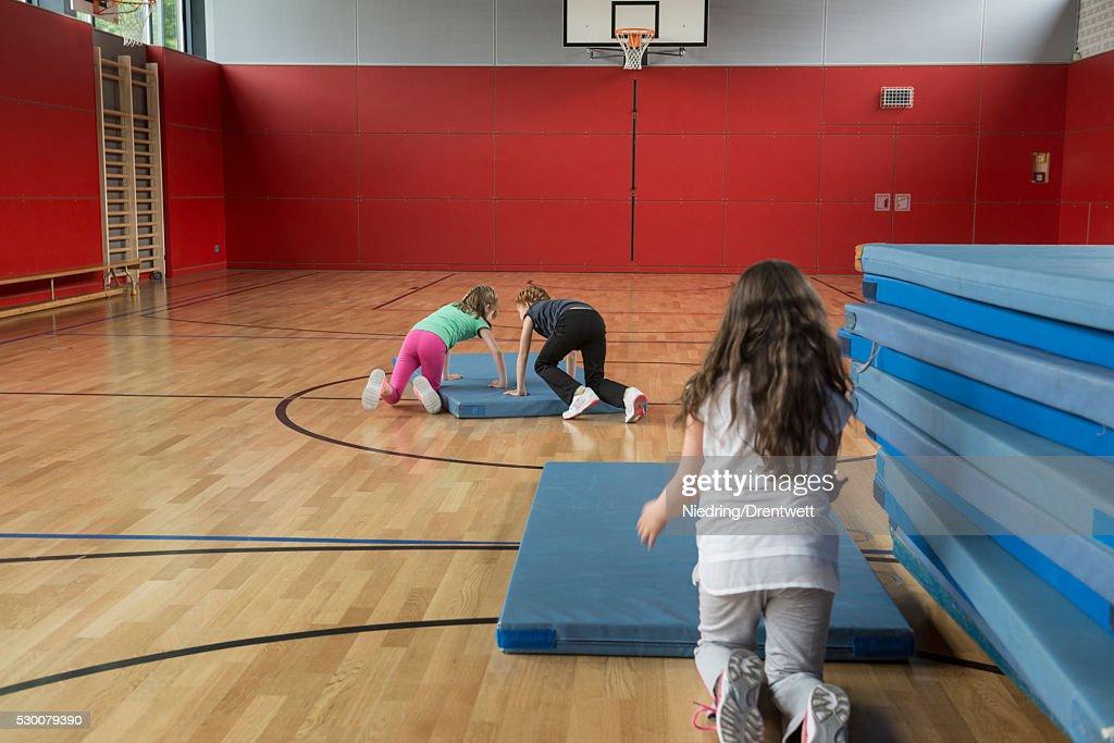 Girls arranging the sports mats in basketball court, Munich, Bavaria, Germany : Stock Photo