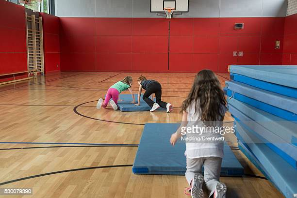 Girls arranging the sports mats in basketball court, Munich, Bavaria, Germany