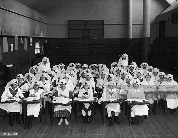 Girls at a school on the East Side of New York, sewing clothing for children in the war zones of France and Belgium, under the auspices of the...
