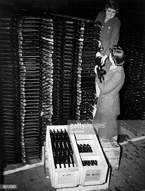 Girls, at an ordnance depot, pack Sten guns into boxes ready to send away to the troops.