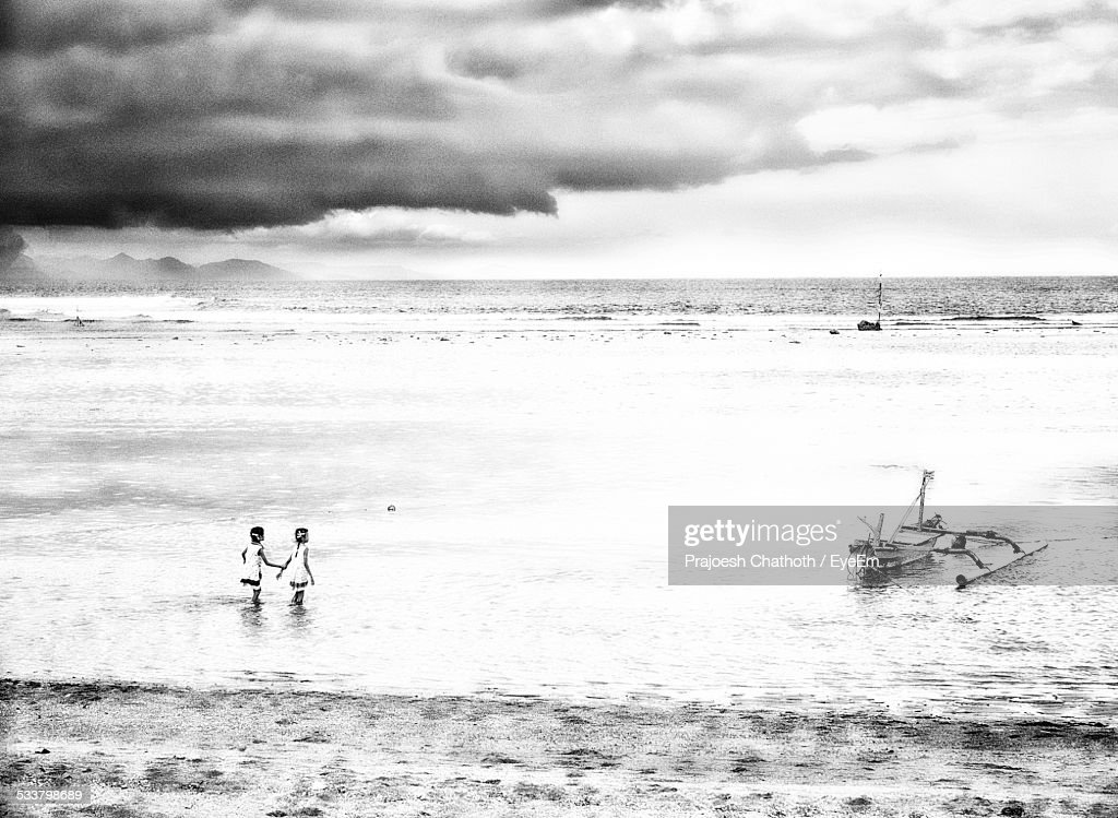 Girls At Beach Against Cloudy Sky : Foto stock