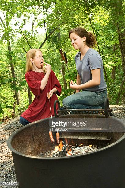 Girls at campfire with burnt hot dog