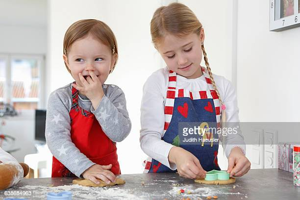 Girls at kitchen counter making cookies smiling