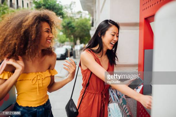 girls at the atm - atm stock pictures, royalty-free photos & images