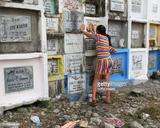 Girls at the tombstone of their deceased kin. Filipinos flock to cemeteries around the country to visit departed relatives and loved ones to remember...