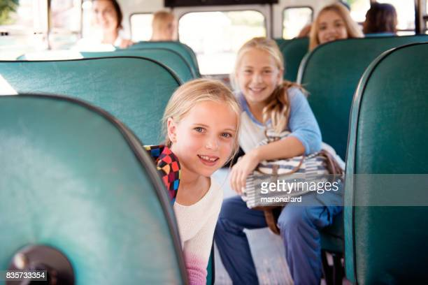 Girls back to school leaning on school bus seat