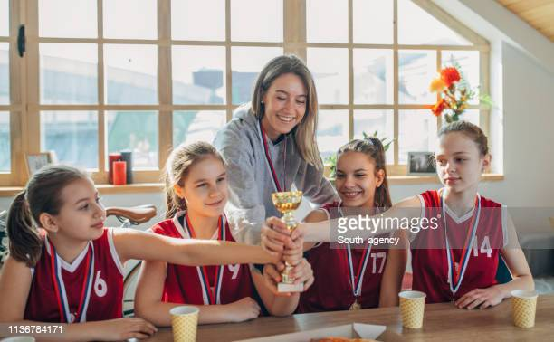 jogadores de basquetebol das meninas e ônibus da senhora que comemoram ganhar um troféu - trophy - fotografias e filmes do acervo