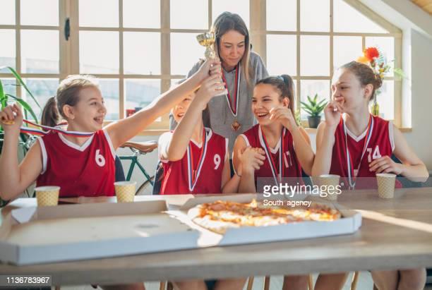 jogadores de basquetebol das meninas e ônibus da mulher que comemoram um troféu em casa - trophy - fotografias e filmes do acervo