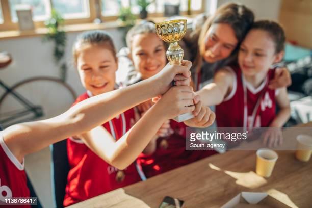jogadores de basquetebol das meninas e ônibus da mulher que comemoram ganhar um troféu - trophy - fotografias e filmes do acervo